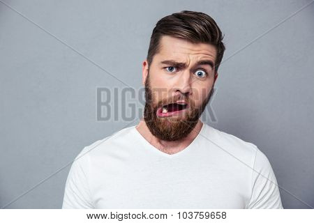 Portrait of a man with stupid mug over gray background