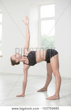 Full length portrait of a pretty girl doing stretching exercises in gym