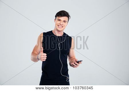 Portrait of a happy sports man holding smartphone with headphones and showing thumb up isolated on a white background