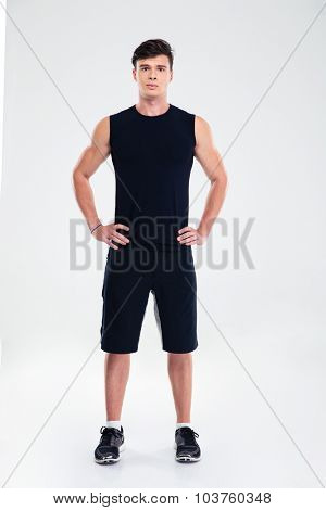 Full length portrait of a handsome man in sports wear standing isolated on a white background and looking at camera