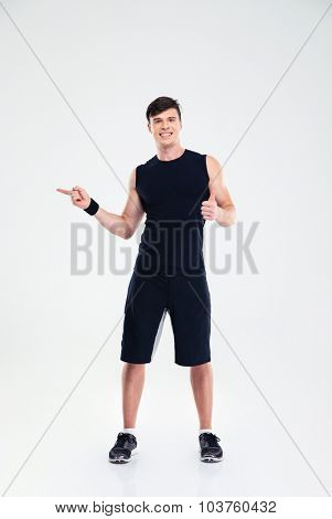 Full length portrait of a smiling fitness man showing thumb up and pointing finger away isolated on a white background
