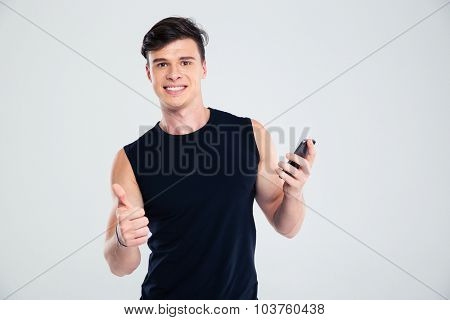 Portrait of a smiling fitness man holding smartphone and showing thumb up isolated on a white background