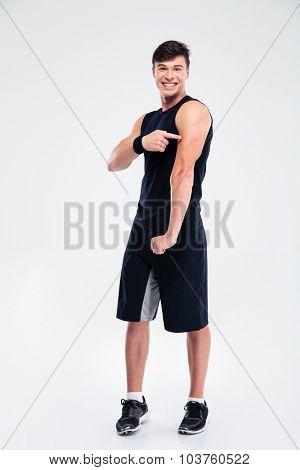 Portrait of a cheerful athletic man pointing finger at his muscles isolated on a white background