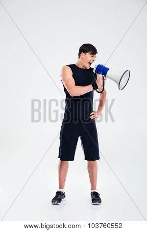 Full length portrait of a fitness man shouting in loudspeaker isolated on a white background