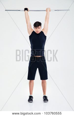 Full length portrait of a fitness man workout with barbell isolated on a white background