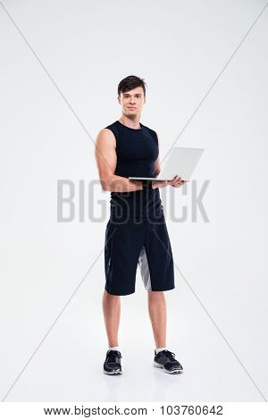Full length portrait of a handsome sports man standing with laptop computer isolated on a white background