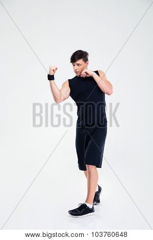 Full length portrait of a sports man boxing isolated on a white background