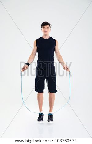 Full length portrait of a man jumping with skipping rope isolated on a white background