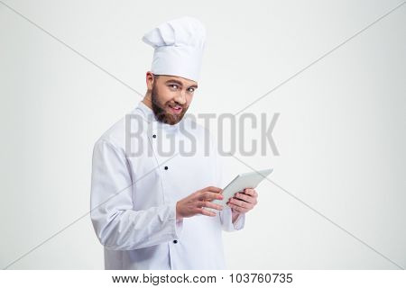 Portrait of a smiling chef cook holding tablet computer isolated on a white background