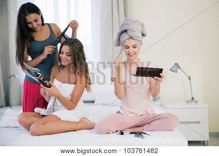 Portrait of a three girlfriends doing makeup and hairstyle at home