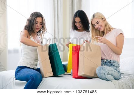 Portrait of a happy three girls with many shopping bags at home