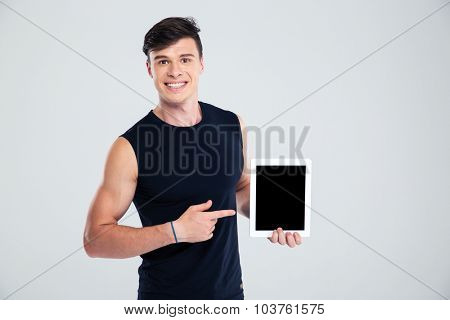 Portrait of a smiling sports man pointing finger on blank tablet computer screen isolated on a white background