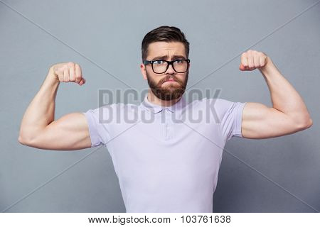 Portrait of a casual man in glasses showing his biceps over gray background