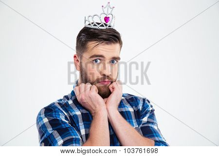 Portrait of a feminine man in queen crown standing isolated on a white background and looking at camera