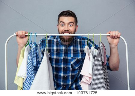 Portrait of a happy hipster man standing with rack of clothes on gray background and looking at camera