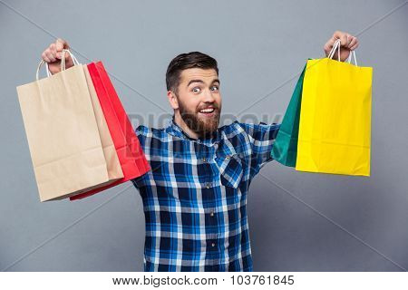 Portrait of a smiling man holding shopping bag over gray background and looking at camera