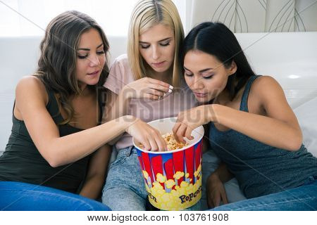 Portrait of a three girlfriends eating popcorn at home
