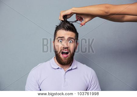 Portrait of a man looking scared while female hands cutting his hair over gray background