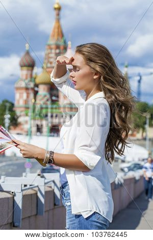 Young beautiful blonde girl holding a tourist map of Moscow, Russia