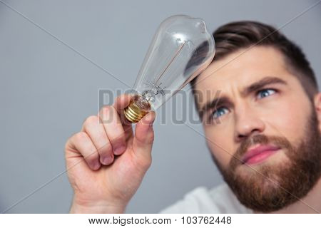 Portrait of a handsome man looking on bulb over gray backgorund