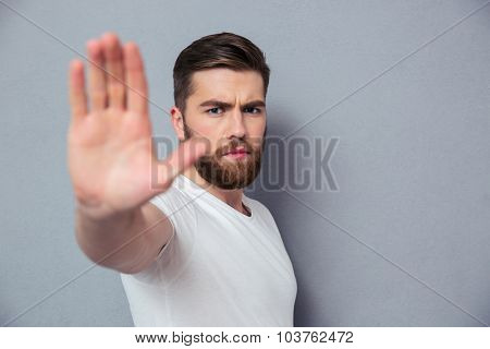 Portrait of a casual man showing stop sign over gray background