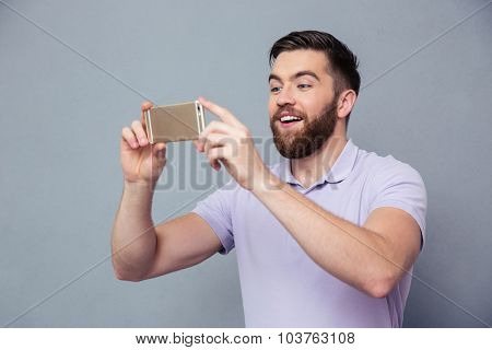 Portrait of a smiling casual man making photo on smartphone over gray background