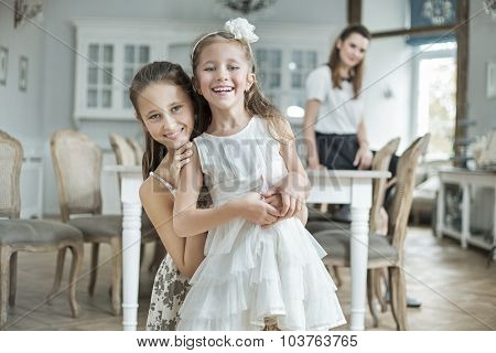 Two sister posing with her mother in a stylish interior