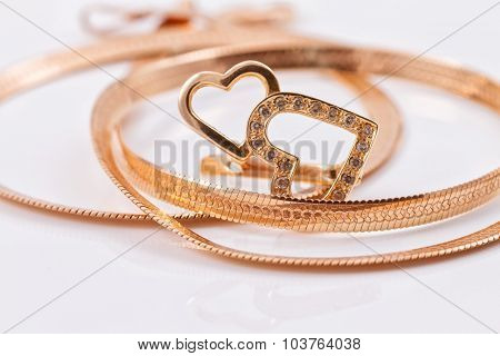 Gold Earrings In The Shape Of A Heart And A Gold Chain