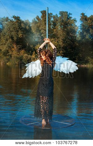 Girl With Angel Wings Standing Near A Pole Dance.