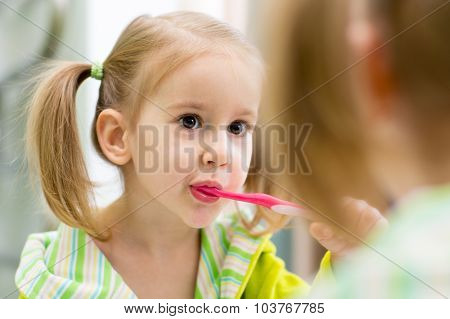child brushes teeth looking at mirror in bathroom