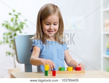 little kid boy playing with educational toys