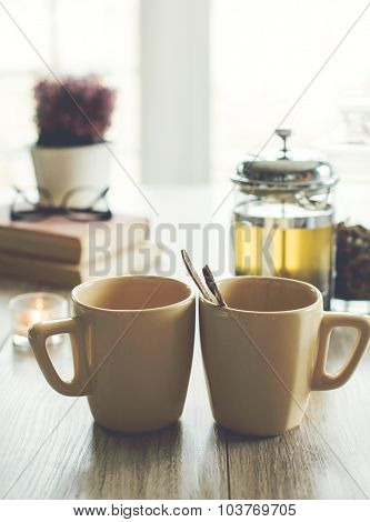Two cups of hot tea on a table with candle, books and glasses on background, selective focus