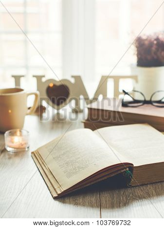 Sweet home. Opened book with glasses, candle and cup of tea on background, selective focus. Text in a book is not recognizable.