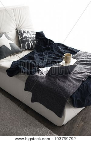 Cozy couch with blanket, coffee and laptop in black and white colors