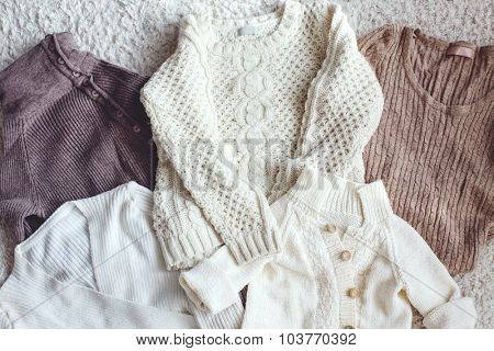 Knitwear closeup, sweaters top view, pastel colors.