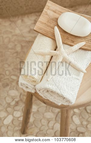 Hotel bathroom decor closeup. White towels, soap, loofah and starfish on wooden stool over pebble floor. Natural colors, still life, top view point.