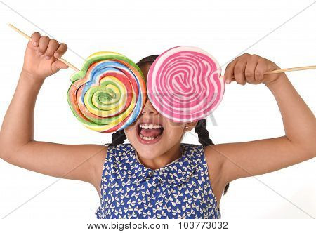 Happy Female Child Wearing Dress Holding Two Big Lollipop In Front Of Her Face Having Fun