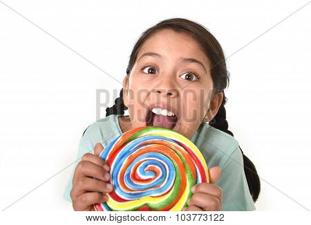 Happy Female Child Holding Big Lollipop Licking The Candy With Her Tongue In Kids Love Candy Concept