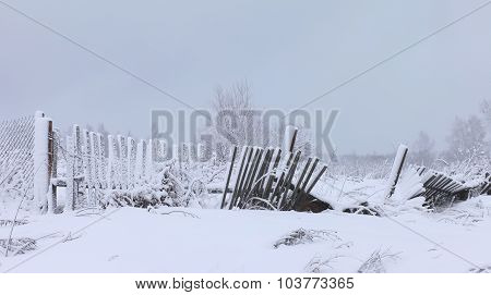 The old rotten fence in a winter white snowy field
