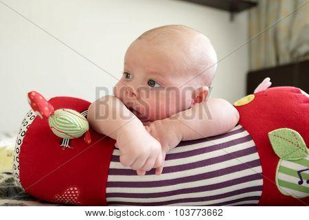 Thinking Baby Boy Lying On A Crawling Roll