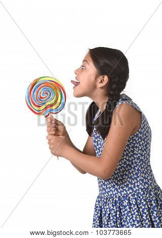 Happy Female Child Holding Big Lollipop Candy Licking The Candy With Her Tongue In Sugar Addiction