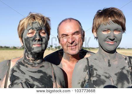 Two Women Covered Mud With Man