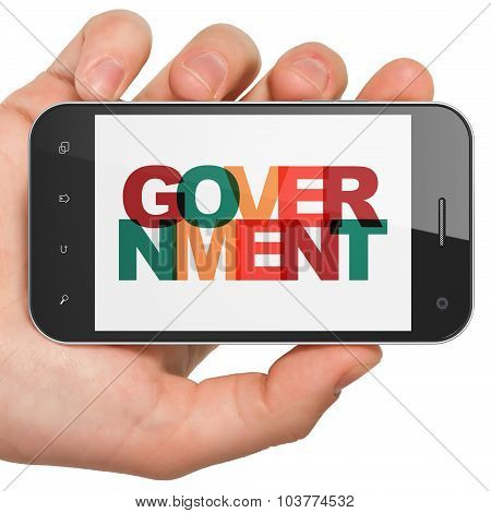 Politics concept: Hand Holding Smartphone with Government on  display