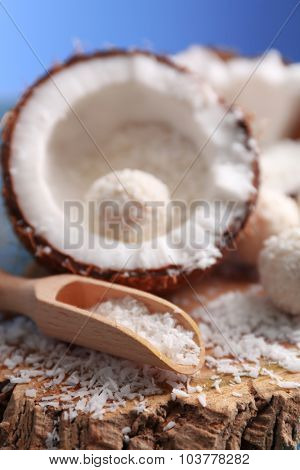 Candies in coconut flakes and fresh coconut on color wooden background