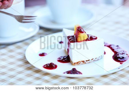Delicious cheesecake with sauce on table in cafe