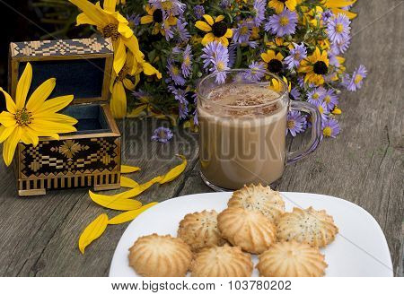 Open Casket, Cappuccino, Plate With Cookies And Wild Flowers On An Old Table