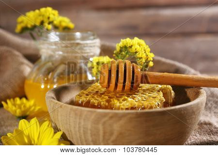 Honeycomb with dipper and jar of honey on sackcloth, close-up