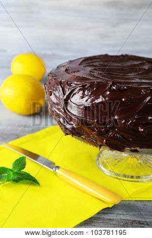 delicious chocolate cake near lemons on grey wooden table