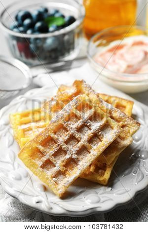 Sweet homemade waffles on plate, on color wooden background