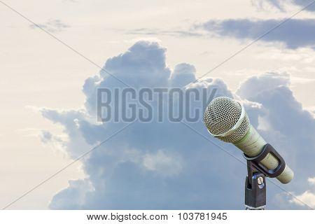 Microphone On A Stand With Blurred Gray Big Cloud Before Raining In The Morning, Copyspace On The Le